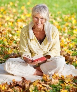 elderly lady in sitting reading a book in the leaves